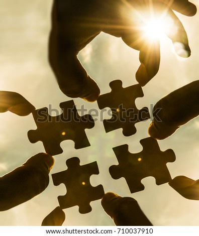 two hands trying to connect 4 puzzle piece with sunset background. Jigsaw alone wooden puzzle against sun rays. four part of whole. symbol of association and connection. business strategy.