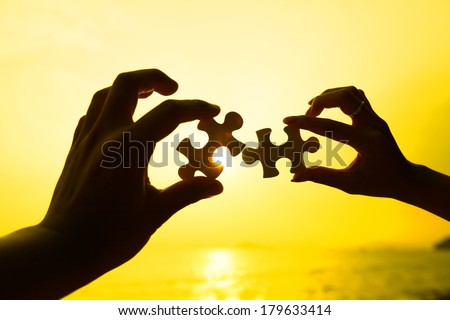 Two hands trying to connect puzzle pieces with sunset background - stock photo