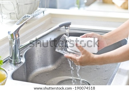 Two hands washing a glass with a sponge under a faucet. - stock photo