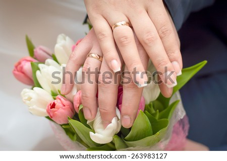 Two hands with gold wedding rings on flower bouquet