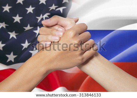 Two hands with partnership hands poses in front of the american and russian flags