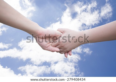 Two hands - woman and man touch each other on sky background - stock photo