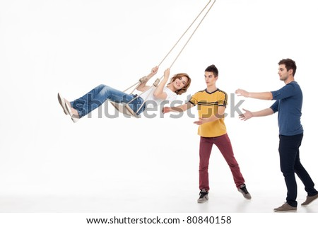 two handsom men pushing on the swing one smiling woman - stock photo