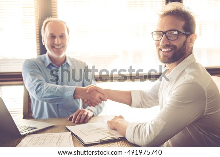 Two handsome businessmen are shaking their hands, looking at camera and smiling while working in office