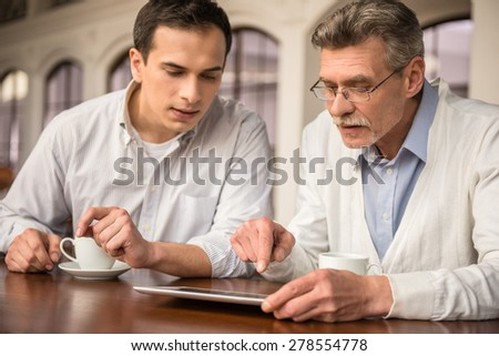Two handsome businessmen in shirts sitting at the wooden table in urban cafe and using digital tablet. - stock photo