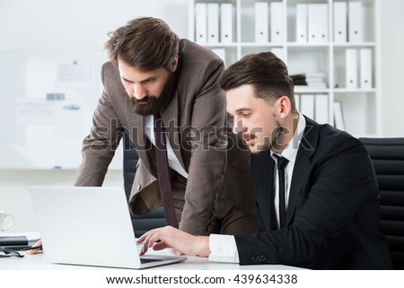 Two handsome businessmen sitting and standing at office desk discussing business project on laptop - stock photo
