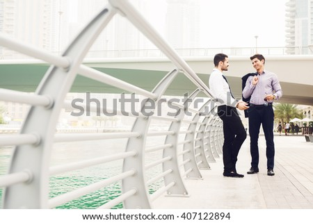 Two handsome businessmen talking at street. - stock photo