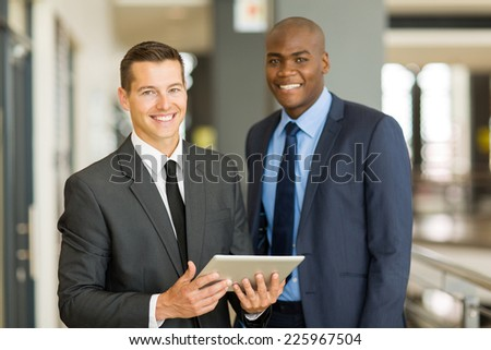 two handsome businessmen using tablet pc in modern office - stock photo