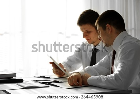 Two handsome businessmen working in office - stock photo