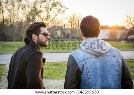 Two handsome casual trendy young men, 2 friends, in an urban park walking and chatting together