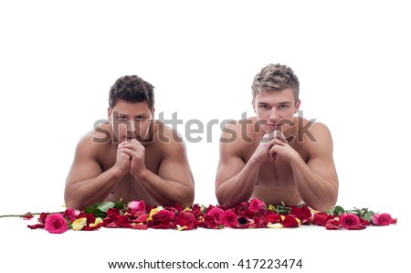 Two handsome guys posing naked with rose petals - stock photo