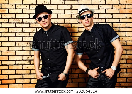 Two handsome men in black shirts and black sunglasses against brick wall. - stock photo