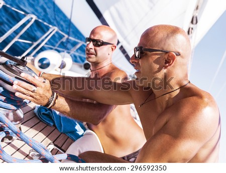 Two handsome shirtless sailors working on sailboat, involved in maritime competition, enjoying water sport, active summer vacation