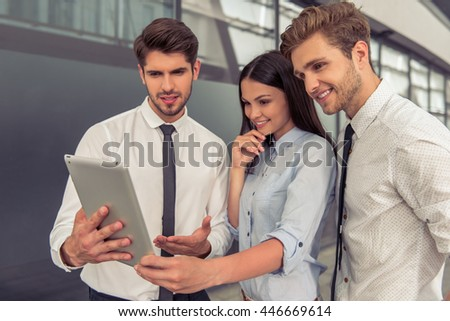 Two handsome young businessmen and lady in classic wear are using a tablet and smiling, standing near the office