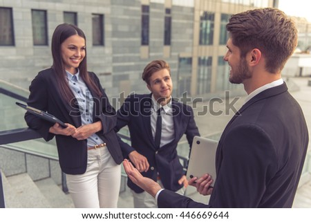 Two handsome young businessmen and lady in formal clothes are talking and smiling, standing on the stairs of the office building