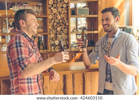 Two handsome young men are drinking beer, talking and smiling, standing near bar counter in a modern urban cafe