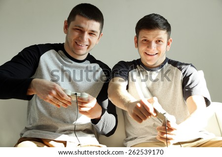 Two handsome young men playing video games in room - stock photo