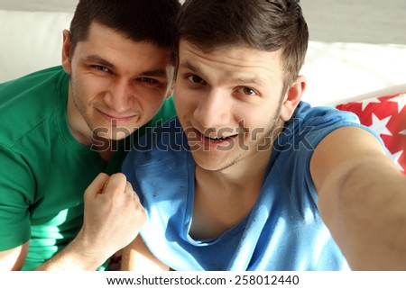 Two handsome young men sitting on sofa and making photo on mobile phone - stock photo