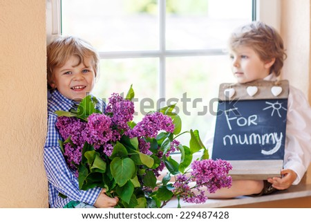 Two happy adorable little sibling boys with blooming lilac flowers and blackboard as gift for their mum on mother's day, indoor. Selective focus on one child. - stock photo