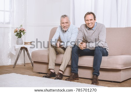 Two happy adult men sitting on sofa in light living room and watching tv
