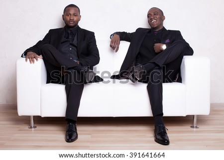 two happy african man businessmen in black suit on white sofa - stock photo
