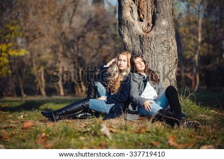 Two happy and cheerful young girl student, blond and brunette in coat and jeans laughing in sunny autumn park full of fallen leaves