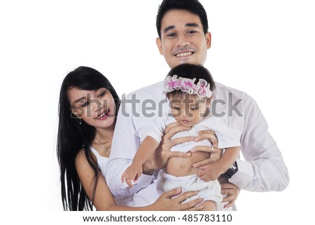 Two happy Asian parents holding their daughter in the studio while smiling at the camera