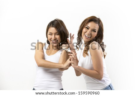 Two happy Asian women standing in front of a white wall.