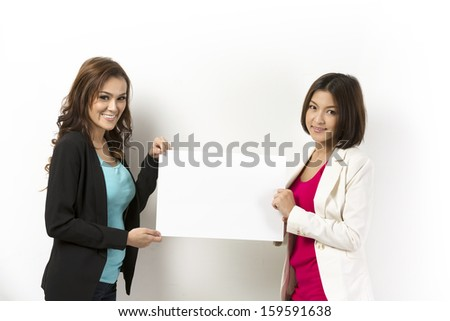 Two happy Asian women with blank board ready for your message. Standing in front of a white wall.  - stock photo