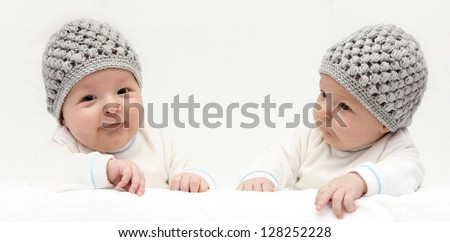 Two happy babies knitted hat - stock photo