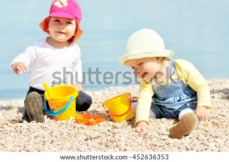 two happy babies playing on the beach