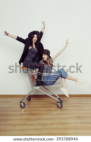Two happy beautiful teen girls driving shopping cart indoors, lifestyle concept