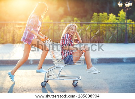 Two happy beautiful teen girls driving shopping cart outdoors, lifestyle concept - stock photo