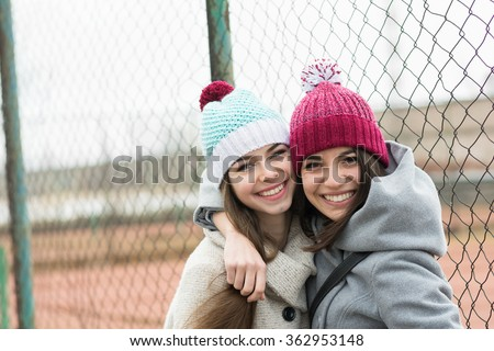 Two happy beautiful teenage girls in knitted beanie hats hugging. Two girlfriends without makeup outdoors in winter smiling and posing. Horizontal, no retouch, no filter, natural light. - stock photo