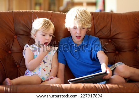 Two happy blonde kids, brother and sister, teenage boy and cute toddler girl, playing together with tablet pc sitting indoors at home in sunny living room on brown leather sofa - stock photo
