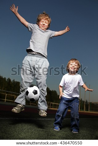 two happy boy jump with  soccer ball on green grass
