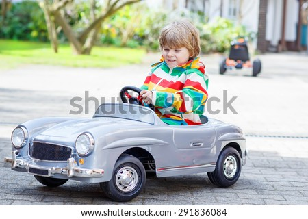 Two happy boys friends playing with big old vintage toy car in spring or autumn garden, outdoors. Active leisure with kids outdoors  on warm spring or autumn day. - stock photo