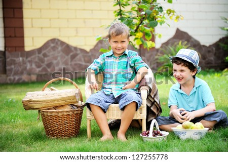 Two happy boys having picnic on a green lawn