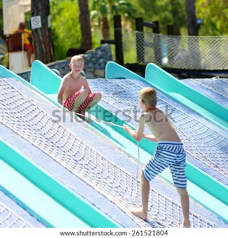 Two happy boys, laughing teenage twin brother, enjoying sunny summer vacation playing and sliding in outdoors swimming pool at waterpark - stock photo