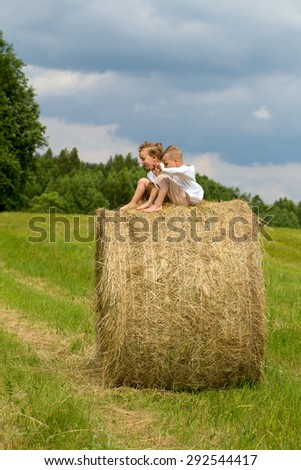 two happy boys on hay bales