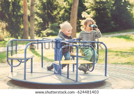 Two happy boys playing on playground in the park. Toned.
