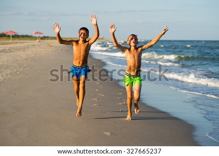 Two happy  boys running on the sea beach at summer.