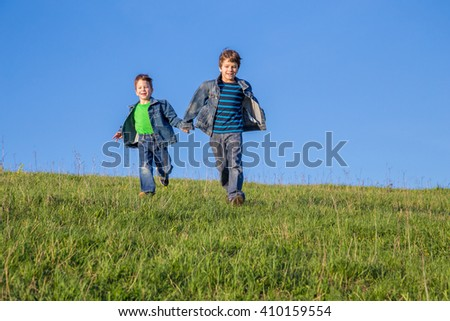 Two happy boys running together on green grass against blue sky