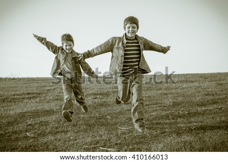 Two happy boys running together on hill, sepia toned