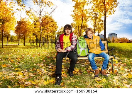 Two happy boys sitting on the bench with backpack in autumn park - stock photo