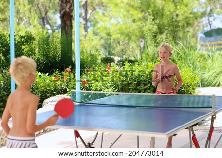 Two happy boys, teenager twin brothers, enjoying summer vacation playing ping pong outdoors - stock photo