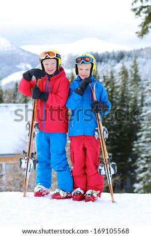 Two happy boys, twin brothers in colorful snowsuits, having fun after skiing in alpine mountains - stock photo