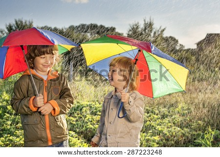 two happy brother with umbrella outdoors - stock photo
