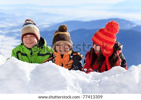 Two happy brothers and sister in woolly hat on snow mountainside in Winter. - stock photo
