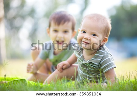Two happy brothers playing on grass in park - stock photo